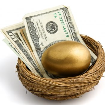 gold egg sitting atop a stack of bills with a one hundred dollar bill on top.  shot on white